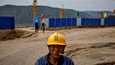 Työmies seisoi uuden hiilivoimalan rakennustyömaan edessä lähellä Qingyangin kaupunkia Kiinassa syyskuussa 2020.