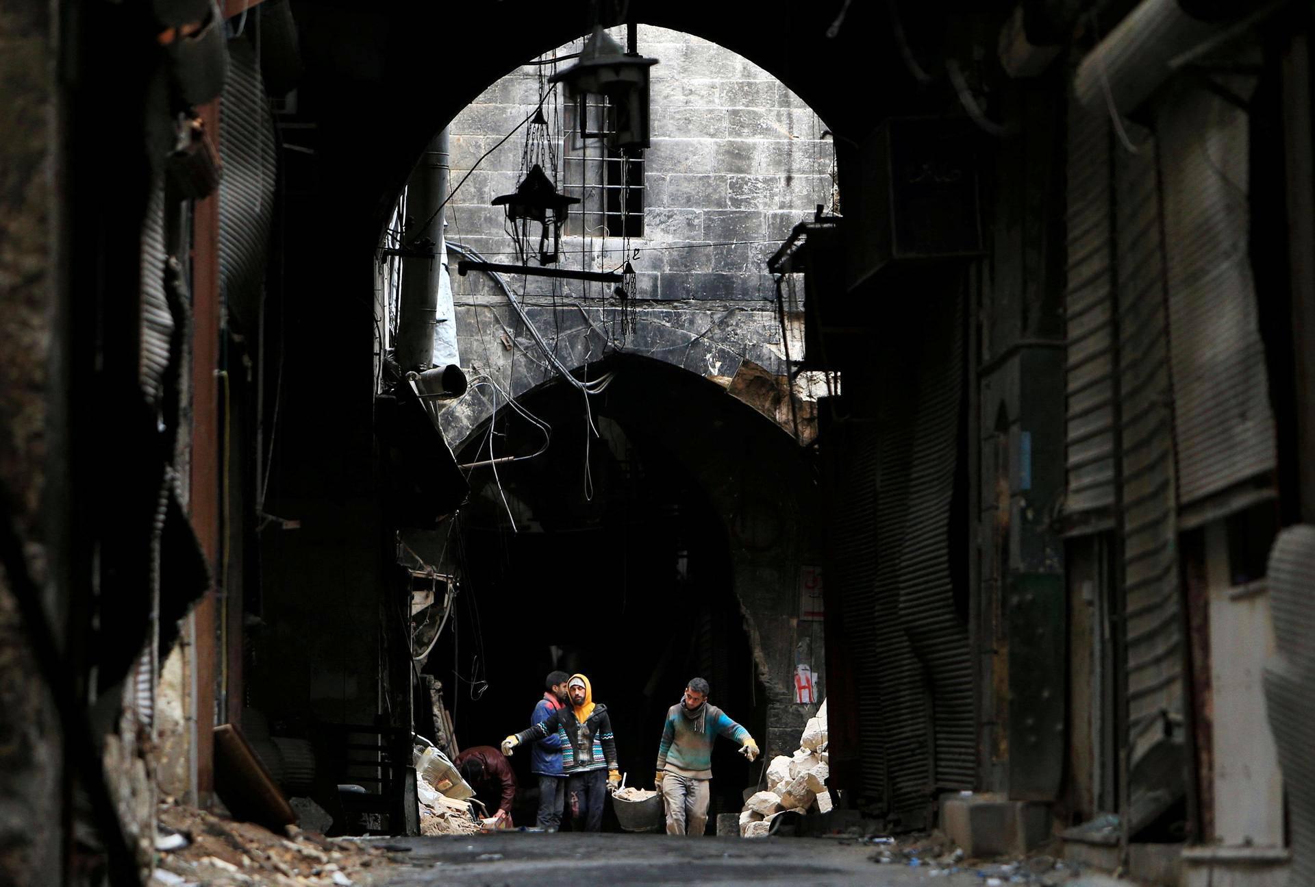 Vapaaehtoiset tutkivat pommitusten tuhoja Khan Gumrukissa Aleppossa.