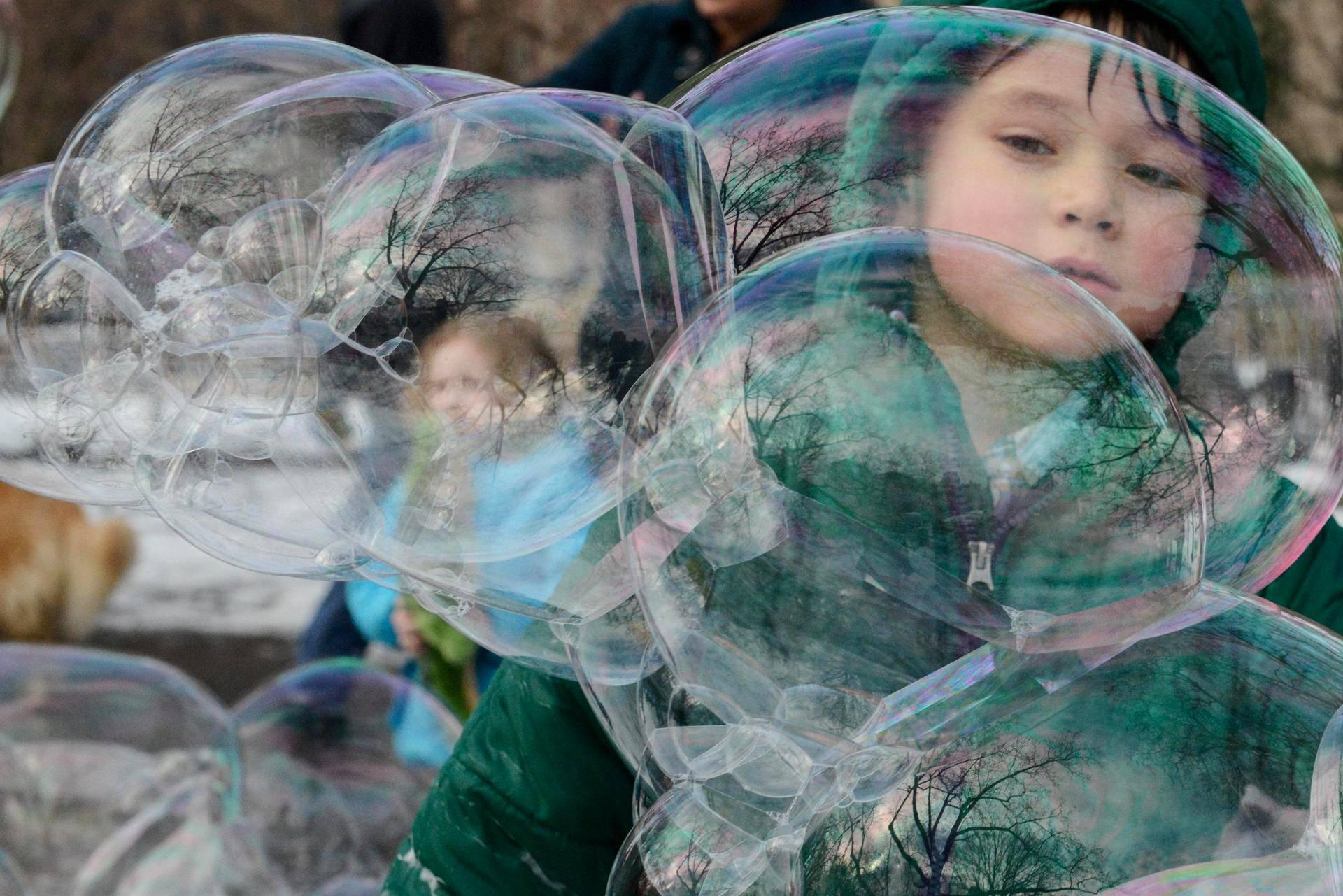 Poika leikki jättimäisten saippuakuplien kanssa Washington-aukiolla New Yorkissa.