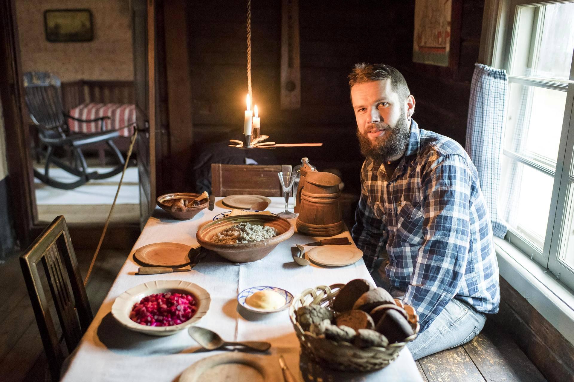 Folkloristi John Björkman Turun Luostarinmäen käsityöläismuseon joulupöydässä. Leipä, puuro ja olut ovat kuuluneet suomalaiseen joulupöytään aina.