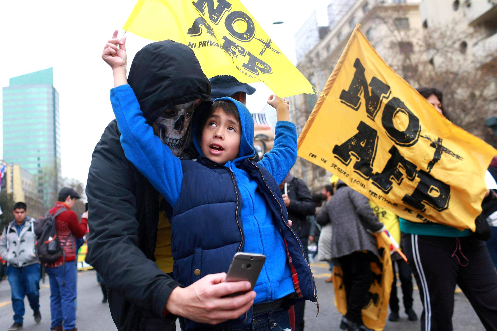 Pääkallomaskiin pukeutunut mielenosoittaja ottaa selfien pikkupojan kanssa Santiagossa sunnuntaina. Kaupungissa osoitettiin mieltä Chilen AFP-eläkejärjestelmää vastaan.