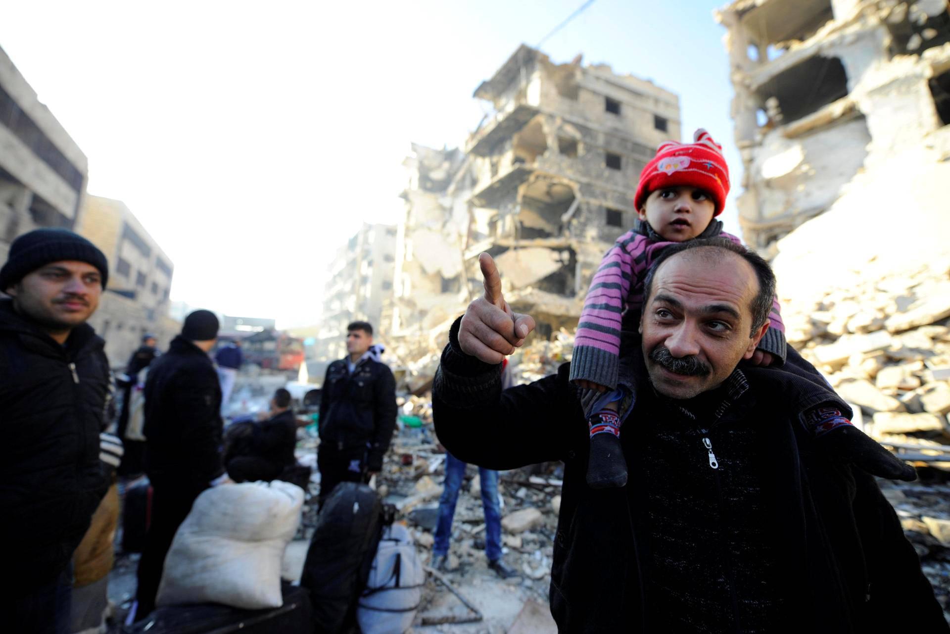 Itä-Alepposta evakuoituja asukkaita hallituksen joukkojen hallinnassa olevalla alueella perjantaina.