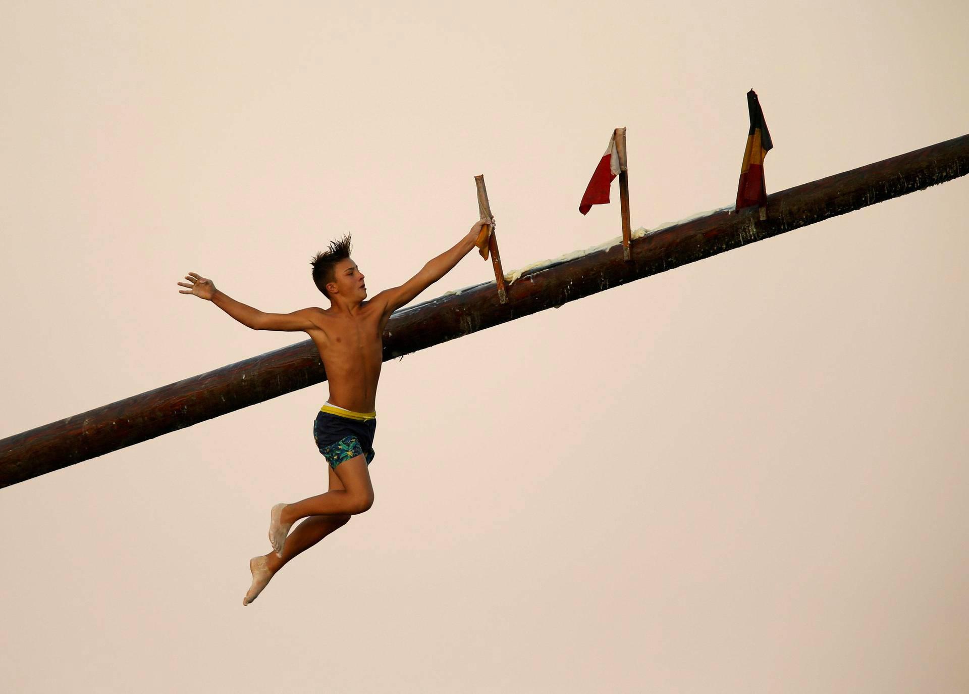 Lapsikilpailija sieppasi lipun pudotessaan puiselta, rasvanpeittämältä paalulta St. Julianin kaupungin suojelijan Pyhän Julianin juhlallisuuksissa. Kyseessä on 1800-luvulta periytyvä leikki, jossa kilpailijat yrittävät kiivetä liukkaan paalun huipulle hakemaan lippua.
