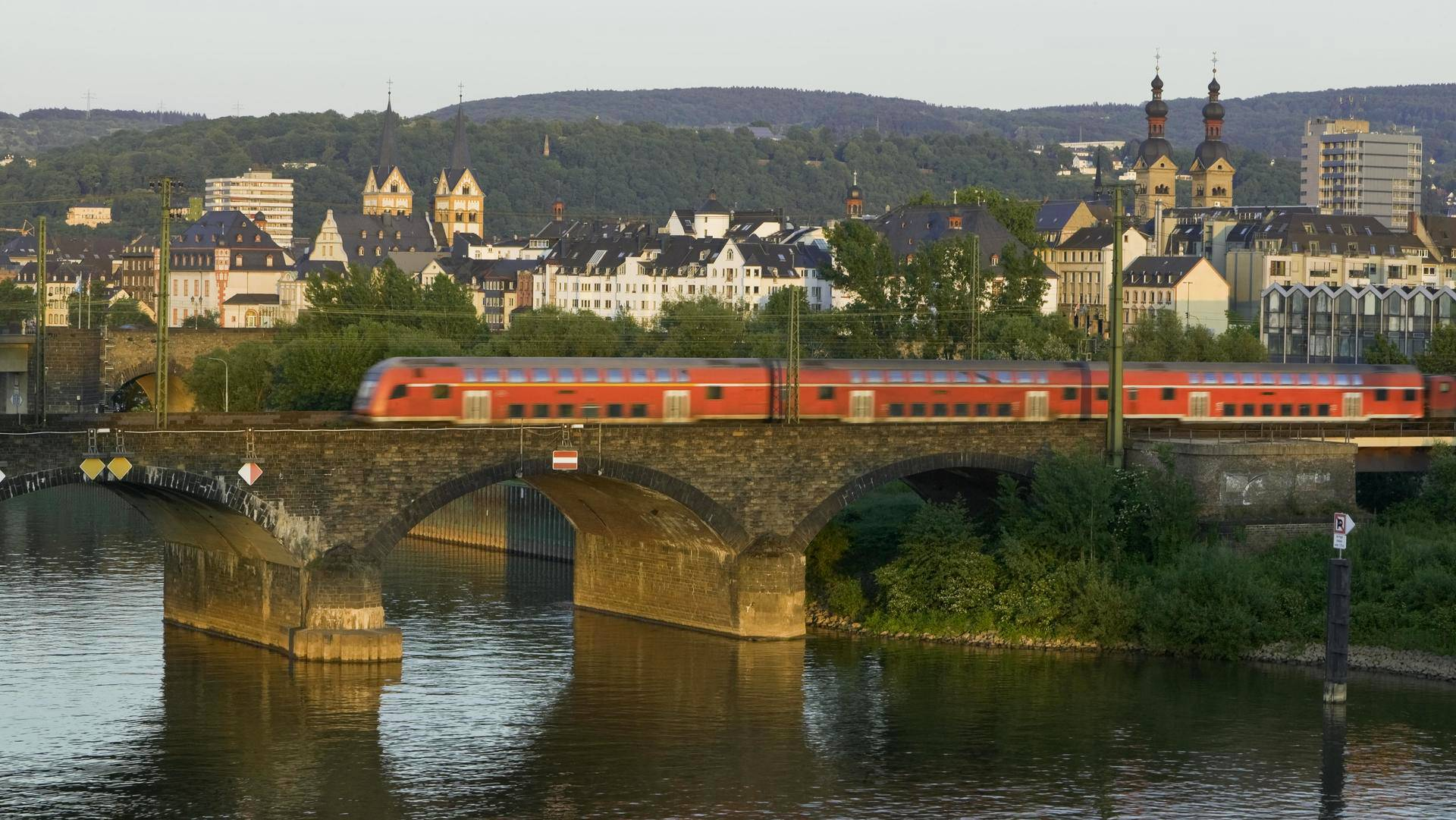 Germany, Koblenz, train crossing bridge over river with cityscape in background