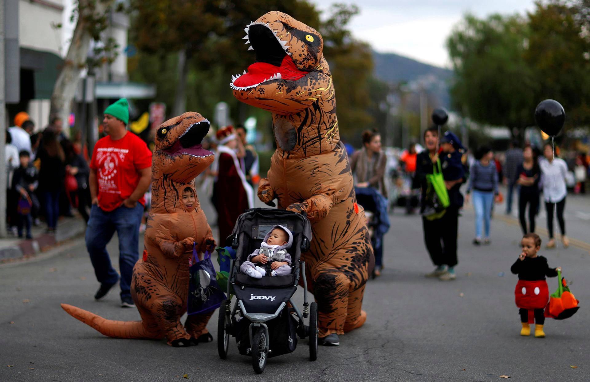 Tyrannosaurus rex -pukuun sonnustautunut halloween-juhlija työnsi lasta vaunuissa Sierra Madressa Kaliforniassa.