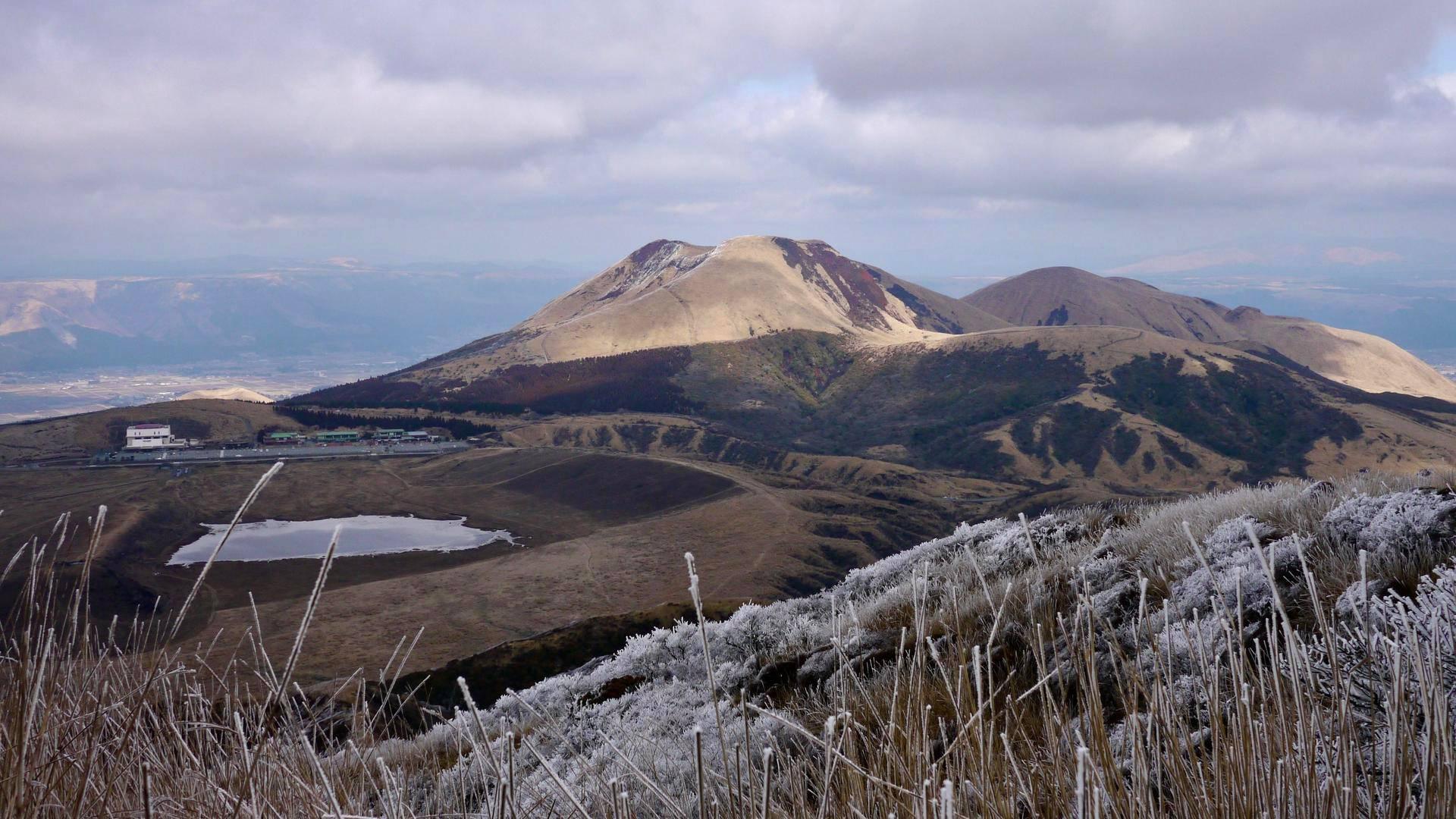 Aso-tulivuori sijaitsee kattilalaaksossa, joka syntyi tulivuoren romahtamisen seurauksena. Yksi Ason huipuista on Kishimadake (oikealla), ja sen takana alhaalla laaksossa on Ason kaupunki. Kishimadakelle lähtee polku Ason tulivuorimuseolta (vasemmalla).