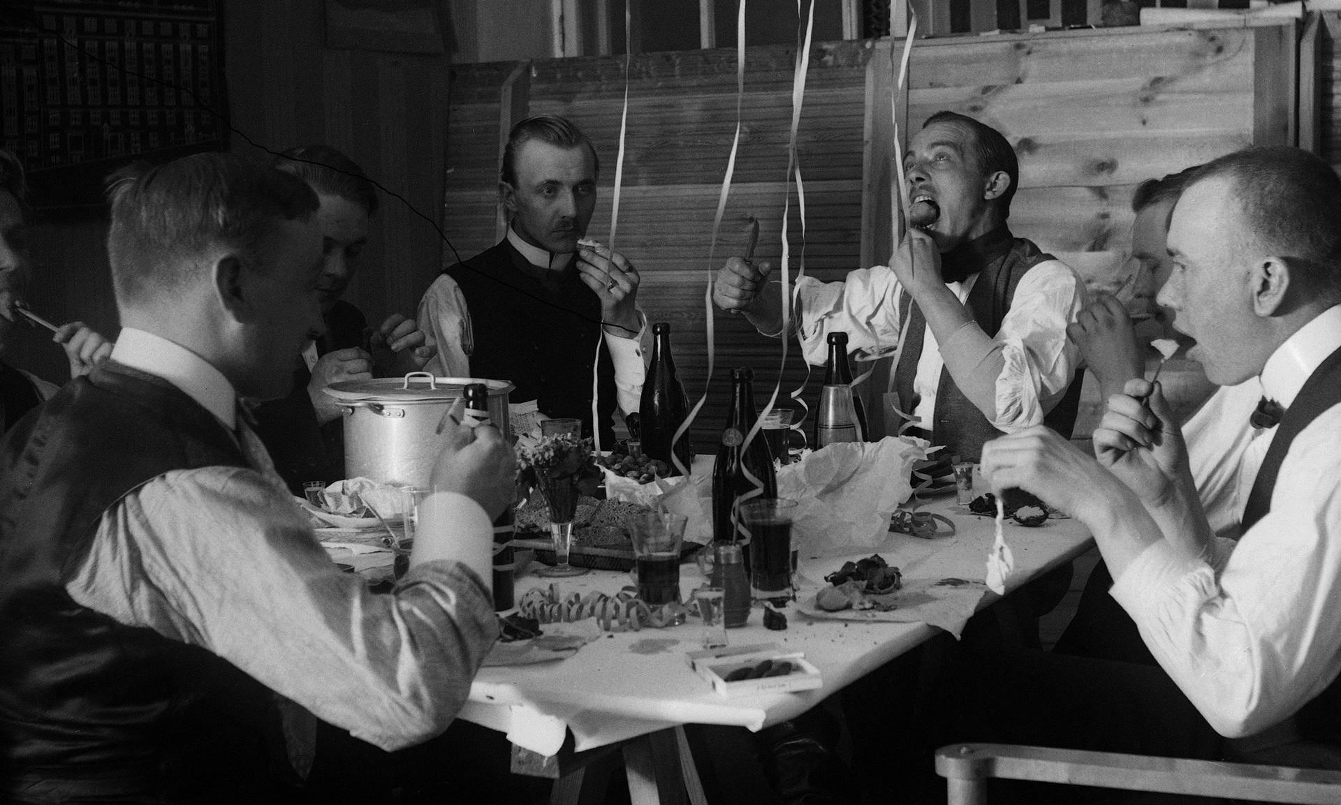 Ryhmä miehiä todennäköisesti juhlimassa vappua tunnistamattoman yhdistyksen tiloissa 1910-luvulla.