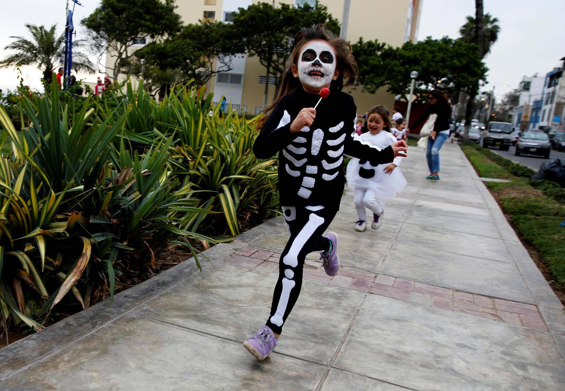 Luurangoksi laittautunut lapsi juoksenteli Limassa, Perussa.