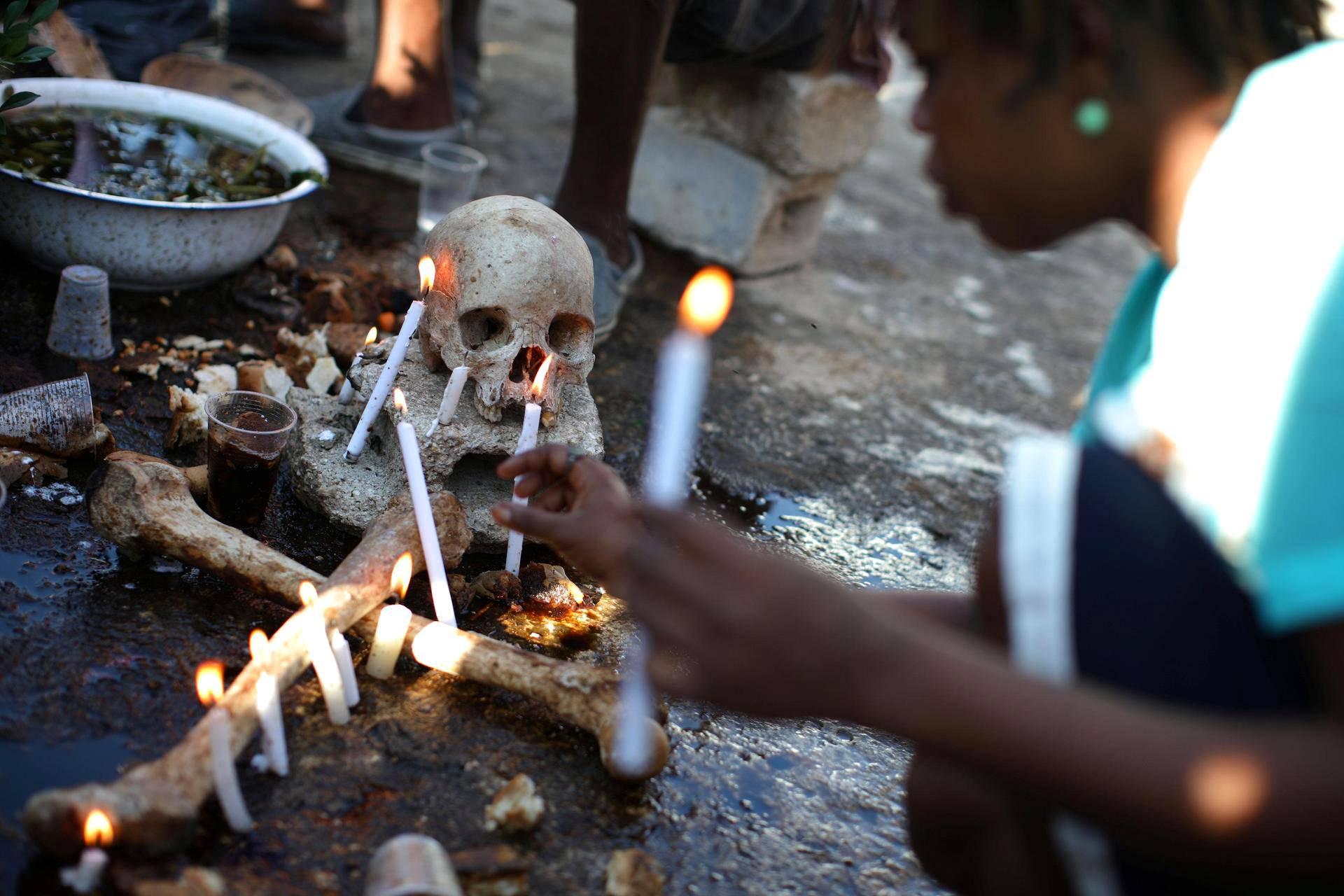Voodoo-uskonnon harjoittaja asetteli kynttilöitä juhlallisuuksissa Port-au-Princessä Haitilla keskiviikkona.