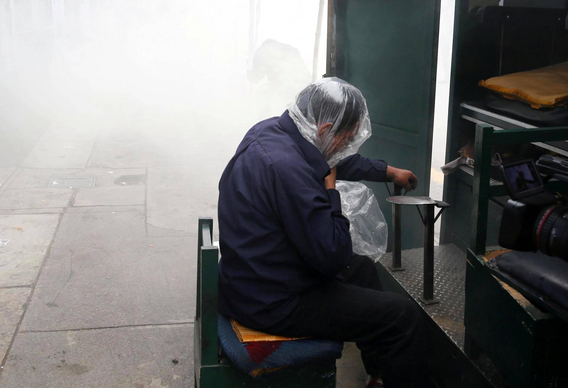 Kengänkiillottaja suojasi muovinpalalla itseään kyynelkaasulta Perun opettajien liiton ja poliisien välisen yhteenoton aikana Limassa. Opettajat vaativat palkankorotuksia ja parempia työoloja.