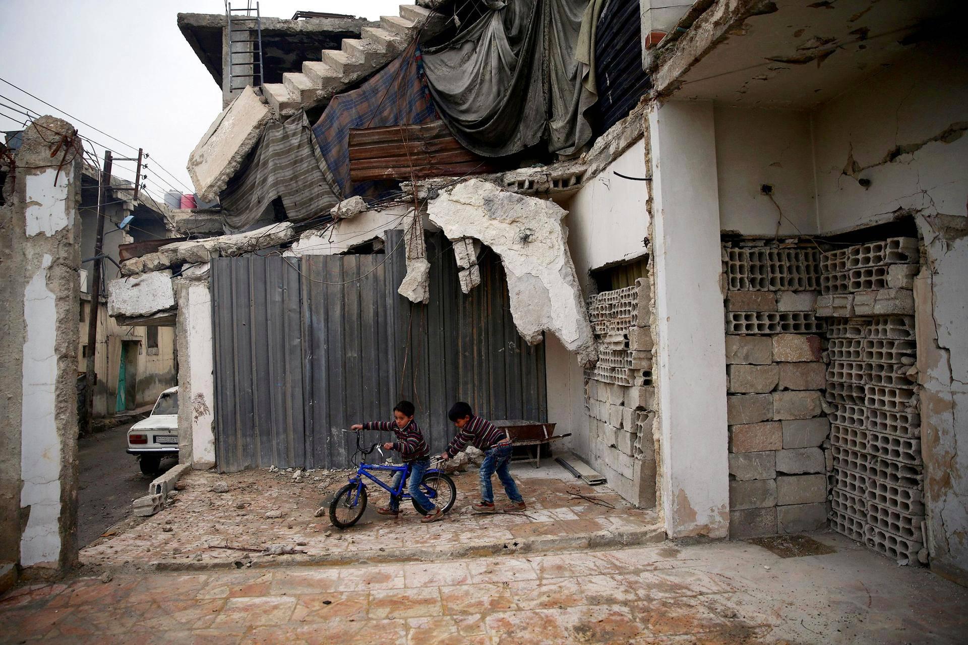 Pojat leikkivät tuhoutuneen talon vieressä Syyriassa, Douman kaupungissa Damaskoksen lähellä.