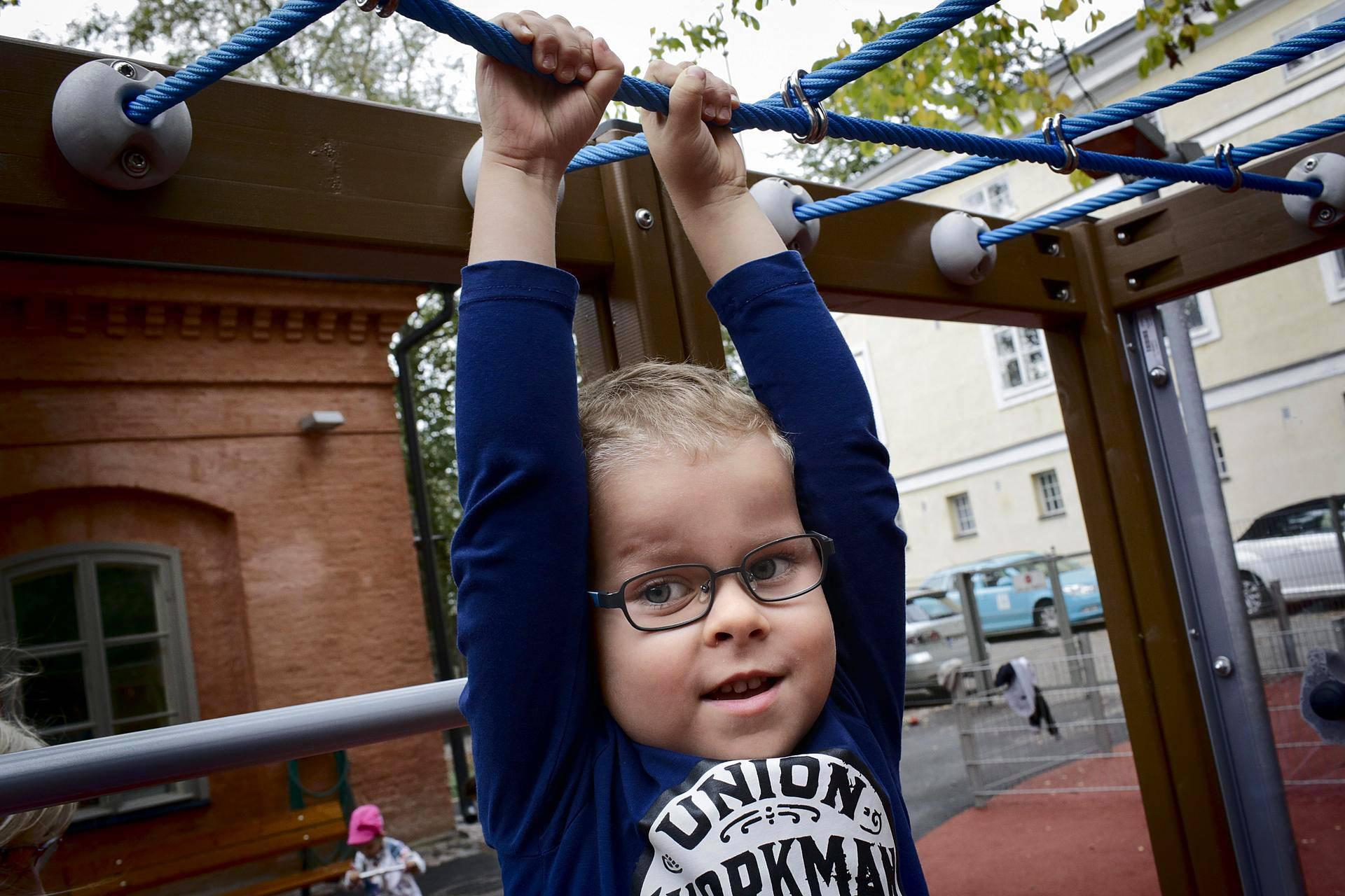 Peetu Päivärinta roikkui kiipeilytelineessä päiväkoti Aleksin pihalla Helsingissä keskiviikkona. Peetulle mieluista liikuntaa on muun muassa juokseminen.
