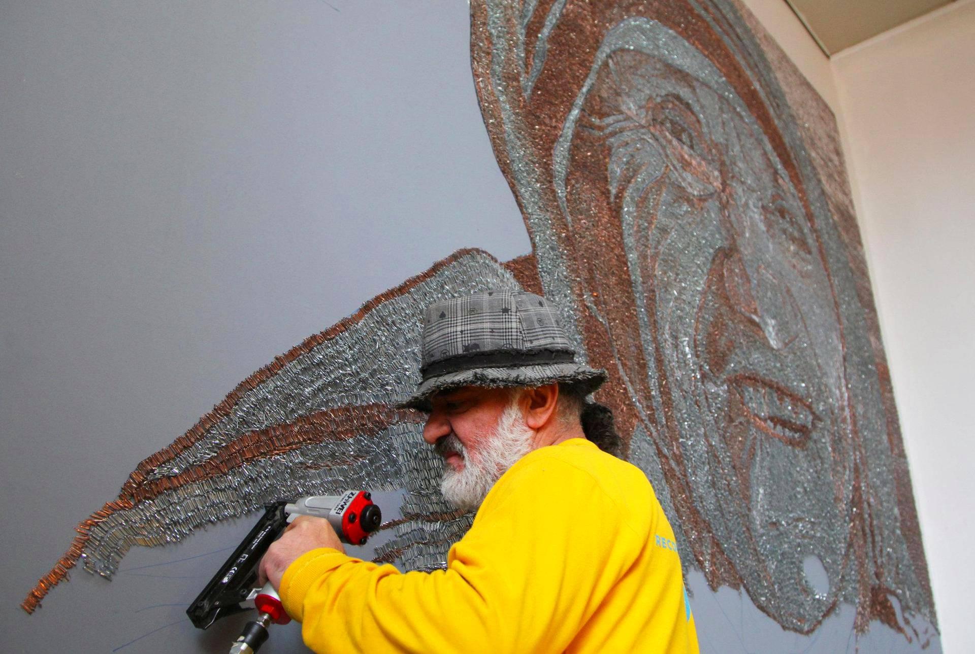 Albanialainen taiteilija Saimir Strati viimeistelee teostaan Äiti Teresasta Pristinassa. Teokseen hän käytti 1,5 miljoonaa kirkasta ja kuparinväristä niittiä.