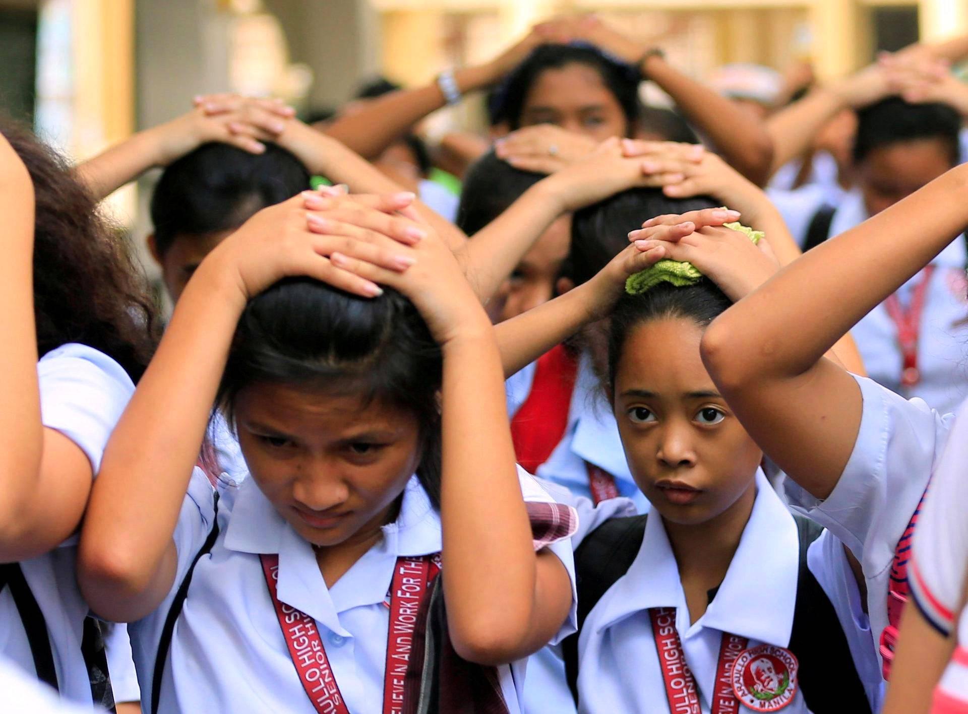 Oppilaat suojelivat päätään, kun heidät evakuoitiin koulutiloista maanjäristyksen jälkeen Manilassa Filippiineillä.