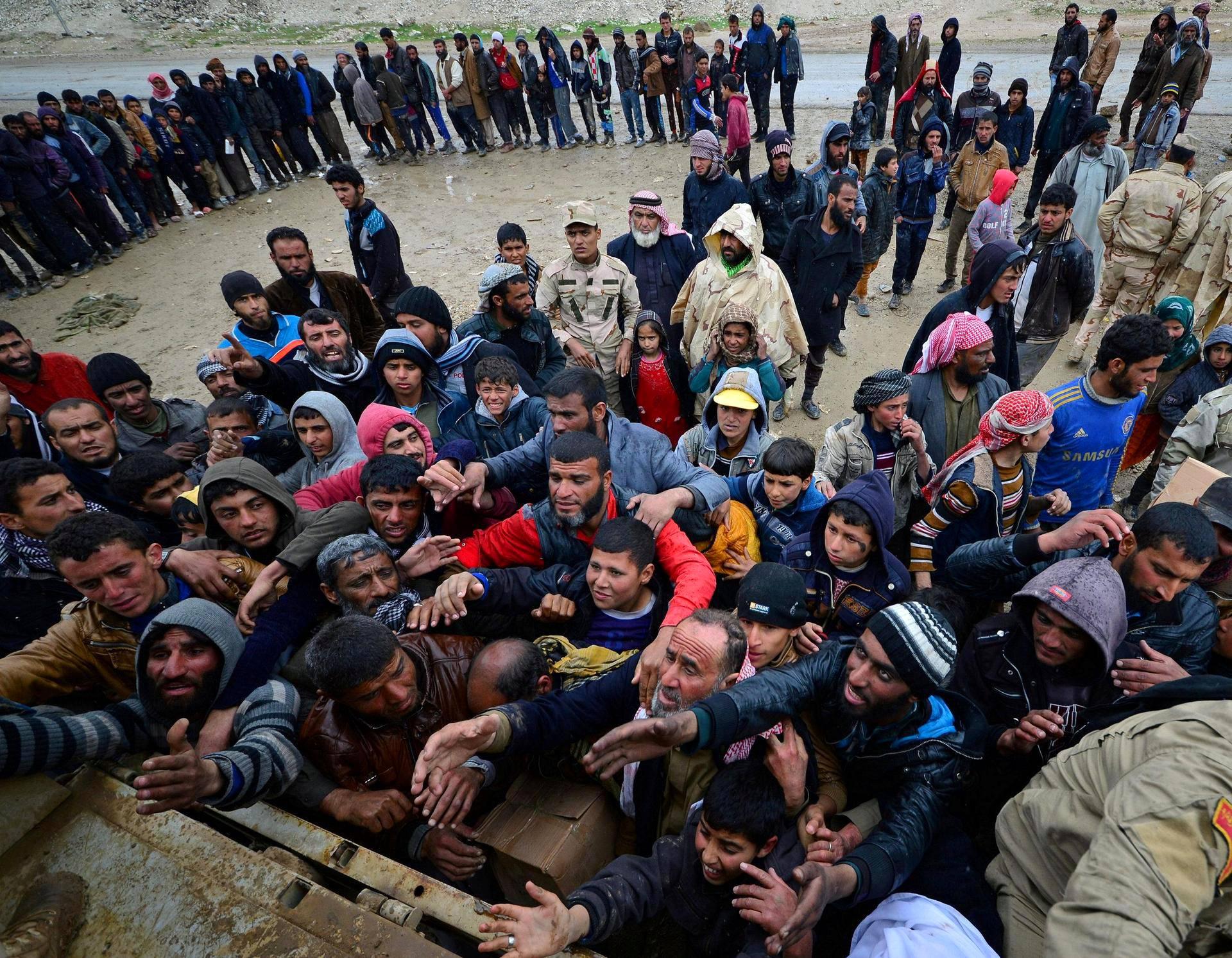 Irakin joukkojen ja Isis-taistelijoiden välisiä taisteluja pakenevat asukkaat jonottivat ruoka-avustuksia Mosulin lähistöllä Badushissa torstaina.