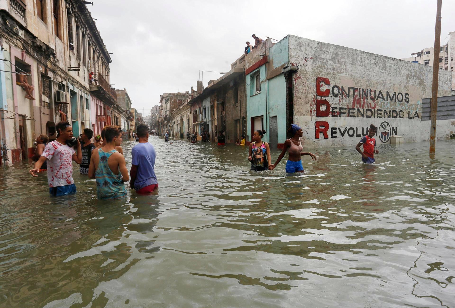 Asukkaat yrittivät edetä vyötärön syvyisessä tulvavedessä Havannan kaduilla sunnuntaina.