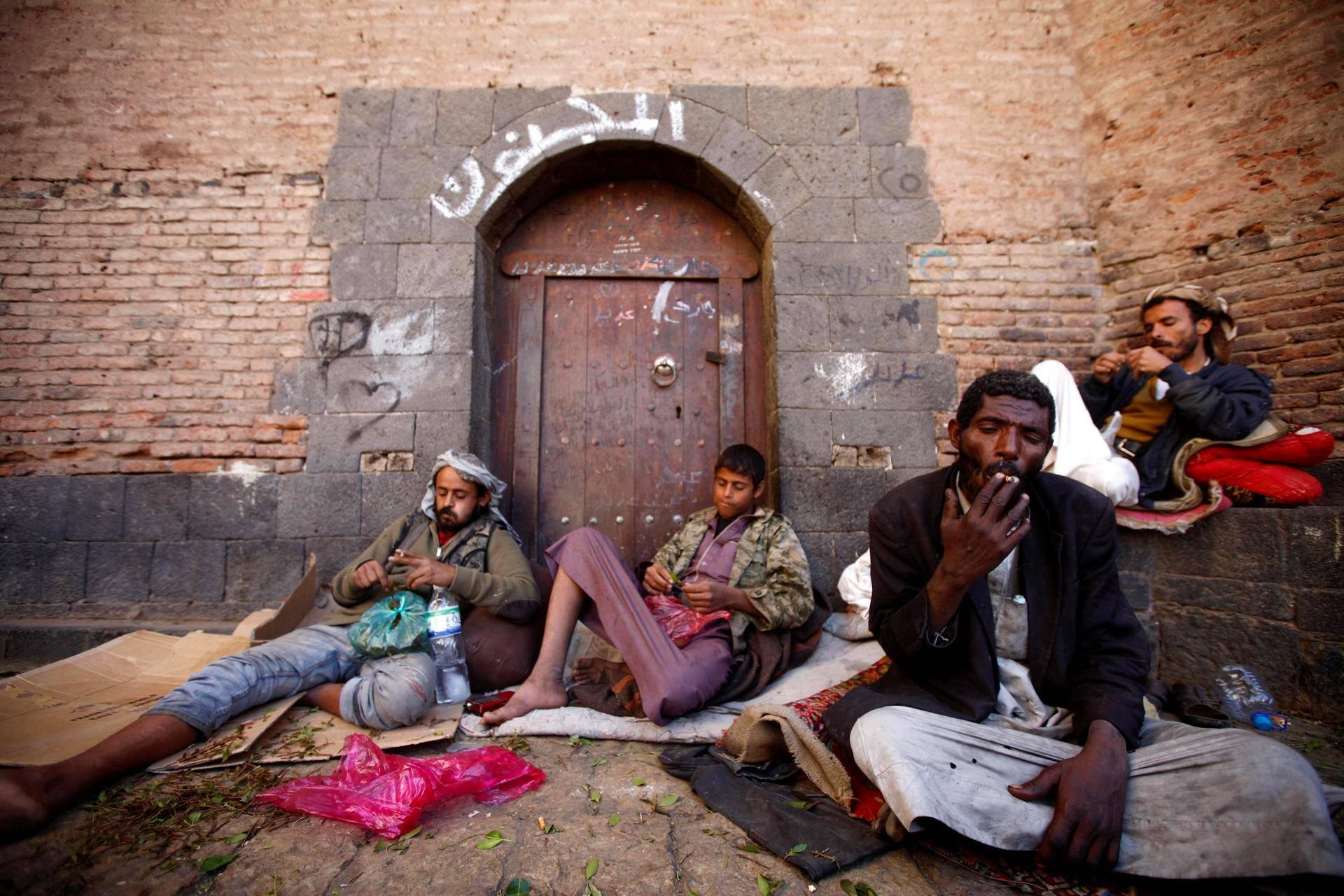 Miehet loikoilivat khatia pureskellen Sanaan vanhassa kaupungissa Jemenissä.
