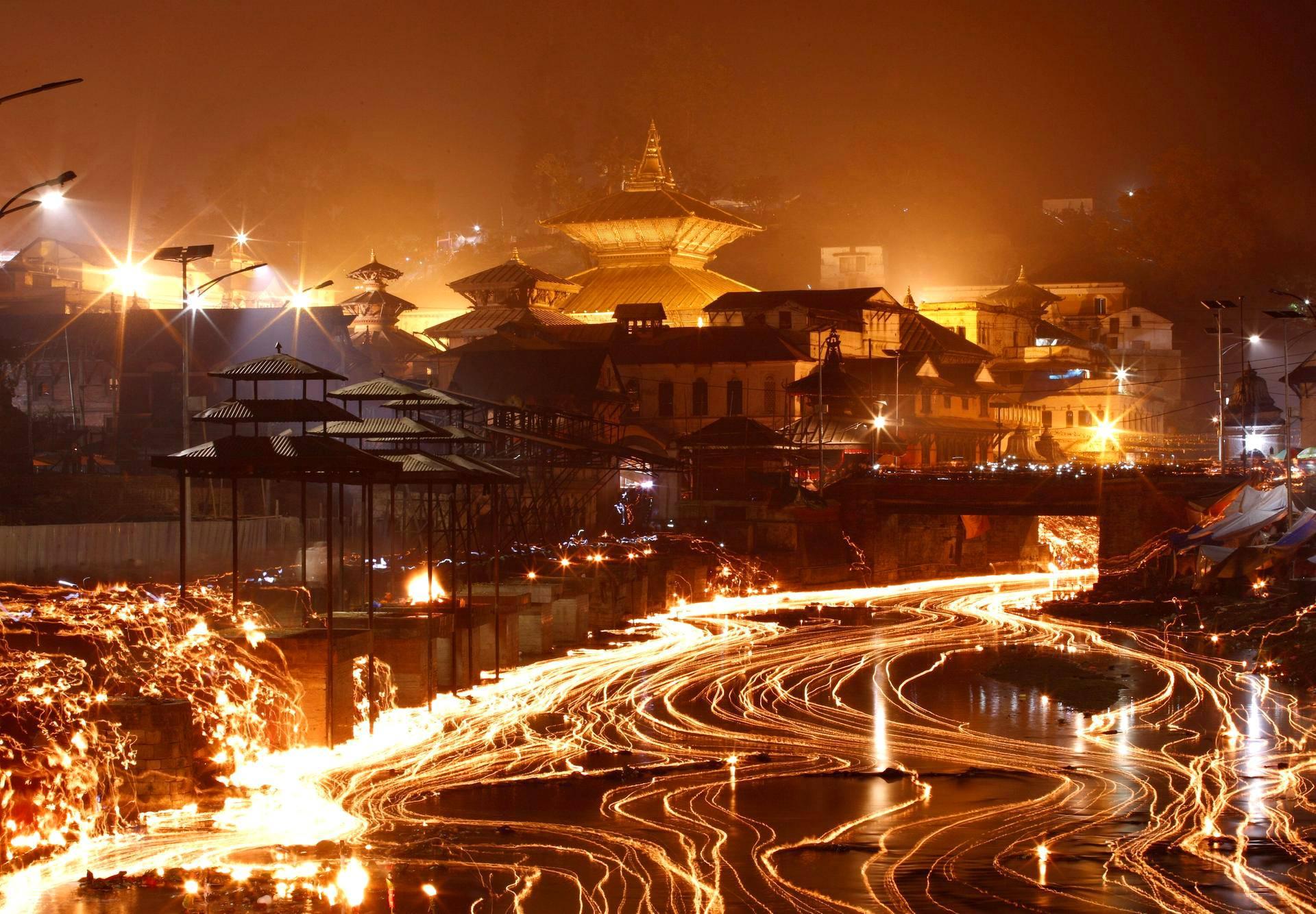 Kynttilät valisevat Bagmati-jokea Pashupatinath-temppelin lähistöllä Nepalin pääkaupungissa Kathmandussa maanantaina. Maassa vietetään Bala Chaturdashi -juhlaa.