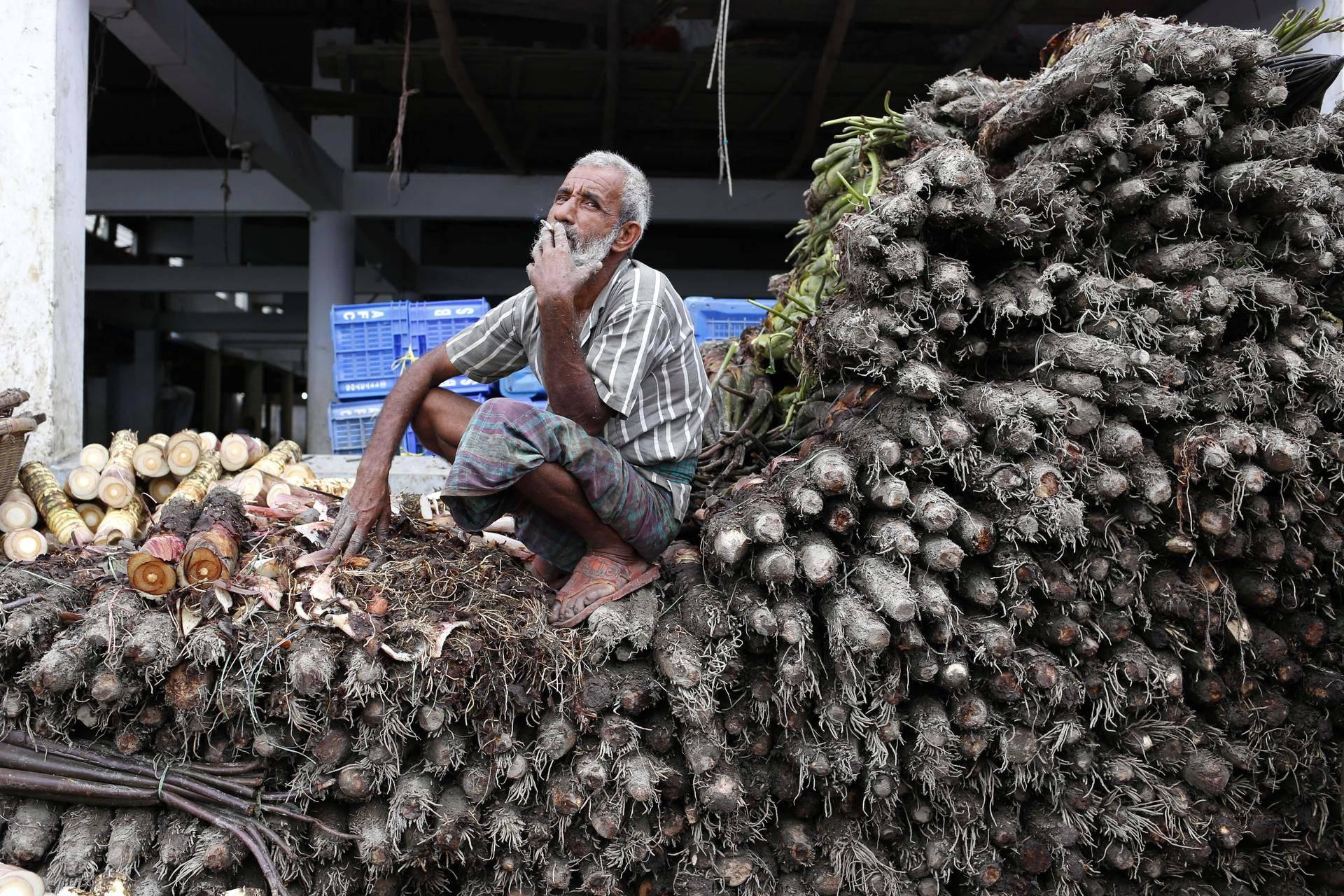 Vanhus piti taukoa lepäämällä vihannesten päällä tukkutorilla Dhakassa, Bangladeshissa.