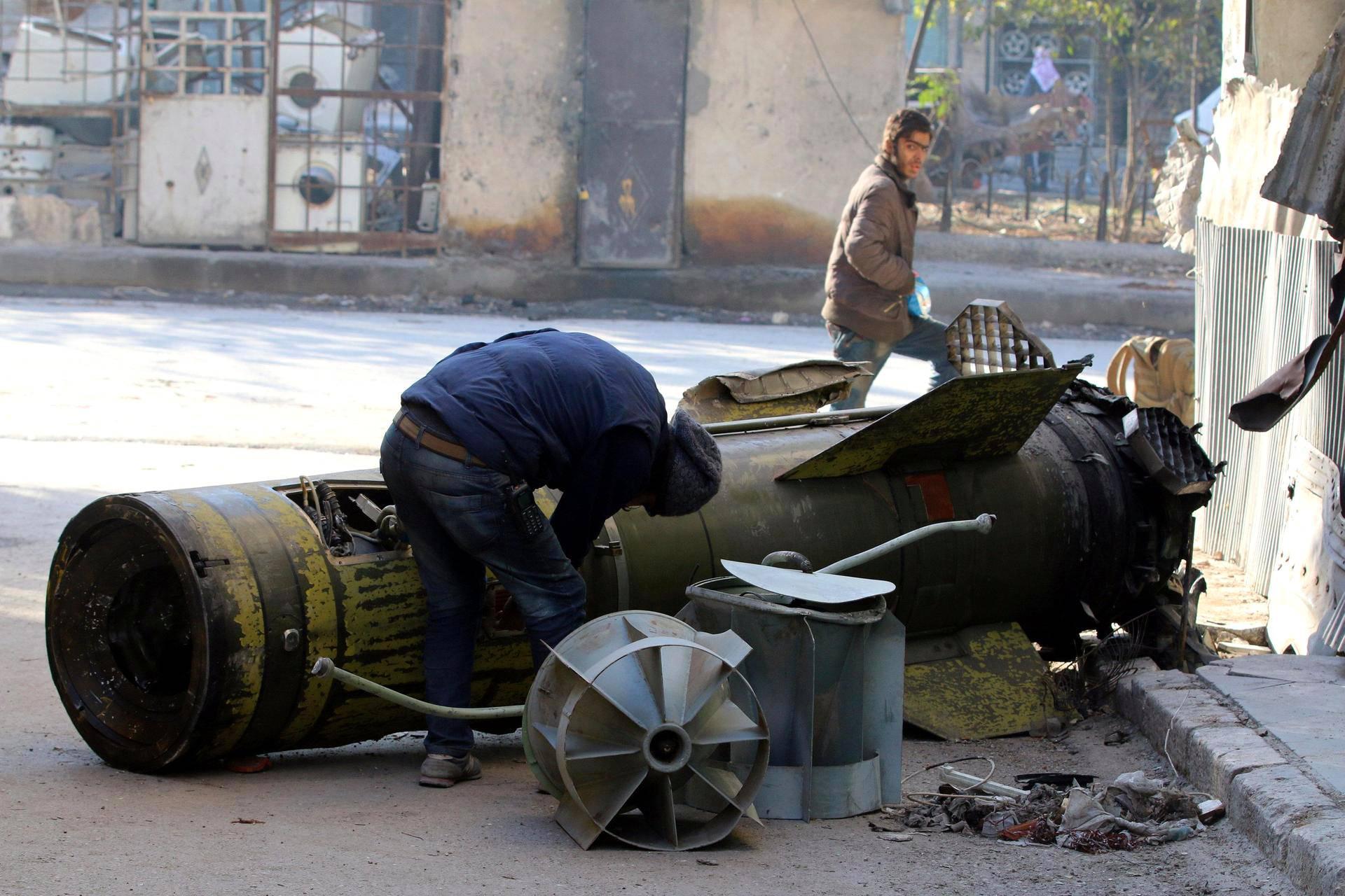 Aleppon asukas tutkii suutariksi jäänyttä hallituksen joukkojen ampumaa ohjusta al-Qaterjin kaupunginosassa maanantaina.