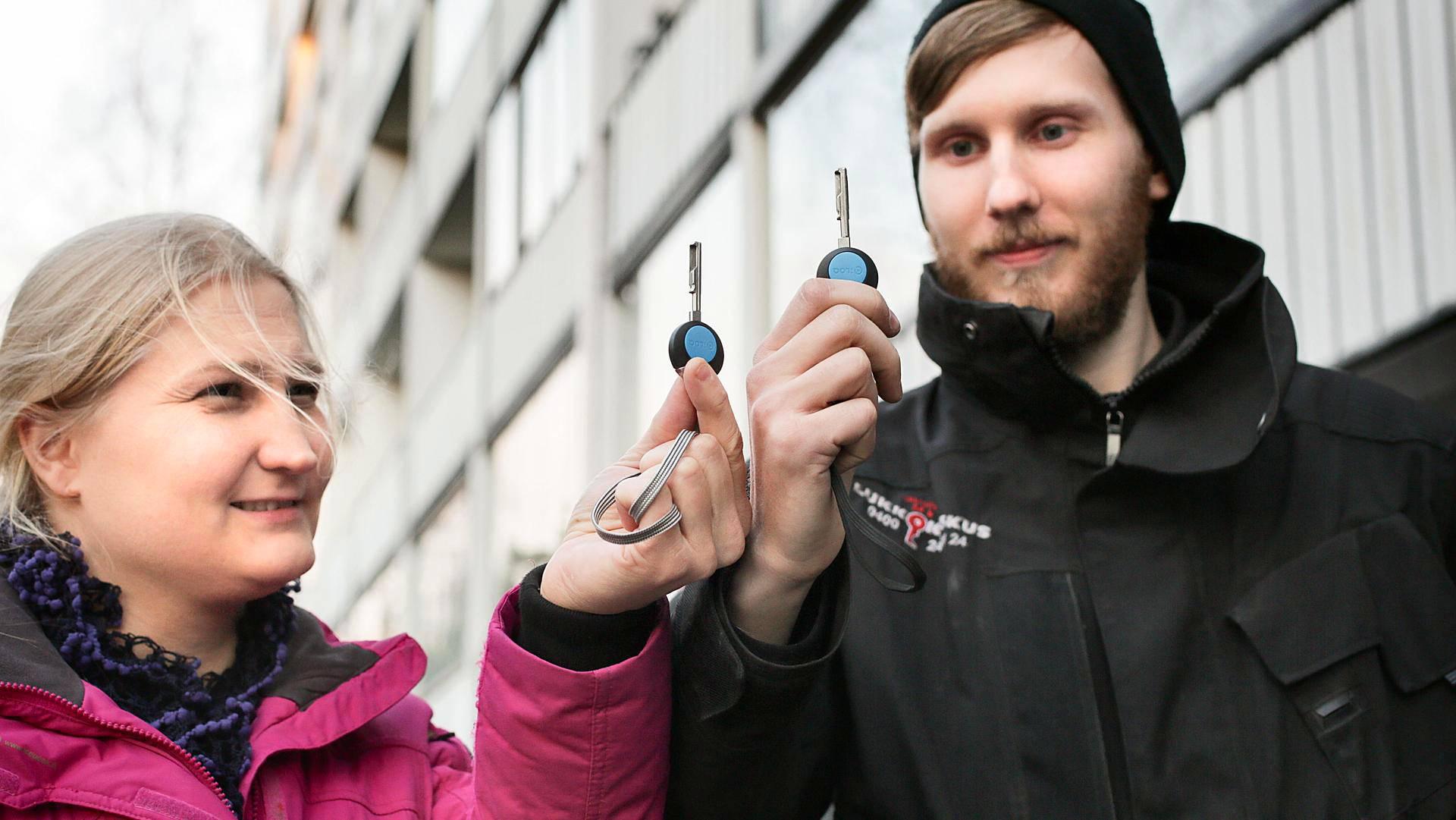 Taloyhtiön hallituksen varapuheenjohtaja Jasmin Juuti sekä lukkoseppä Pauli Leppilahti esittelevät Keinulaudantie 5:n uusia sähköisiä avaimia.