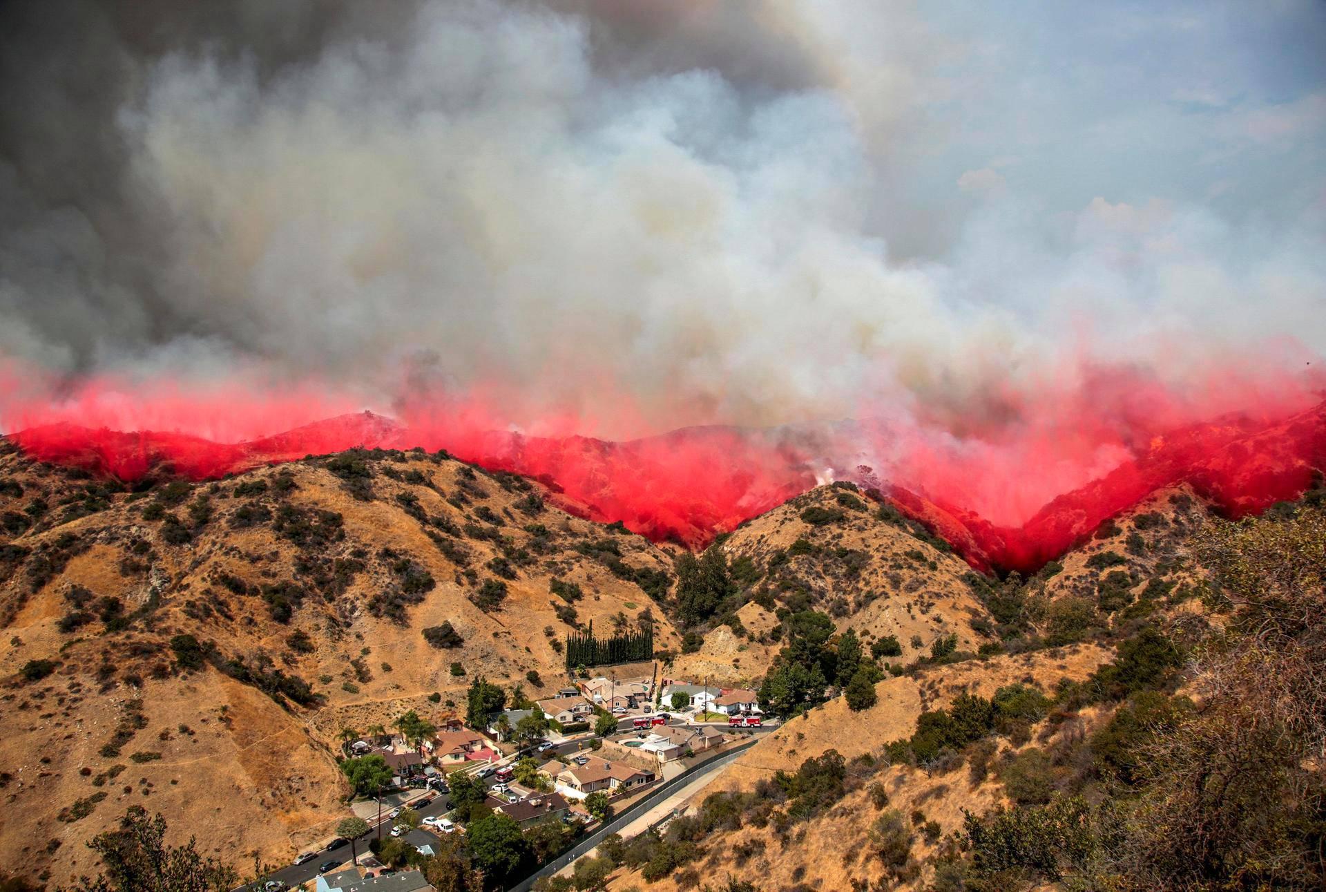 Kalifornian Burbankissa sijaitsevan La Tuna -kanjonin rinteille syntyy punainen raita, kun lentokoneesta on pudotettu sammutuskemikaaleja roihuavan maastopalon päälle lauantaina.