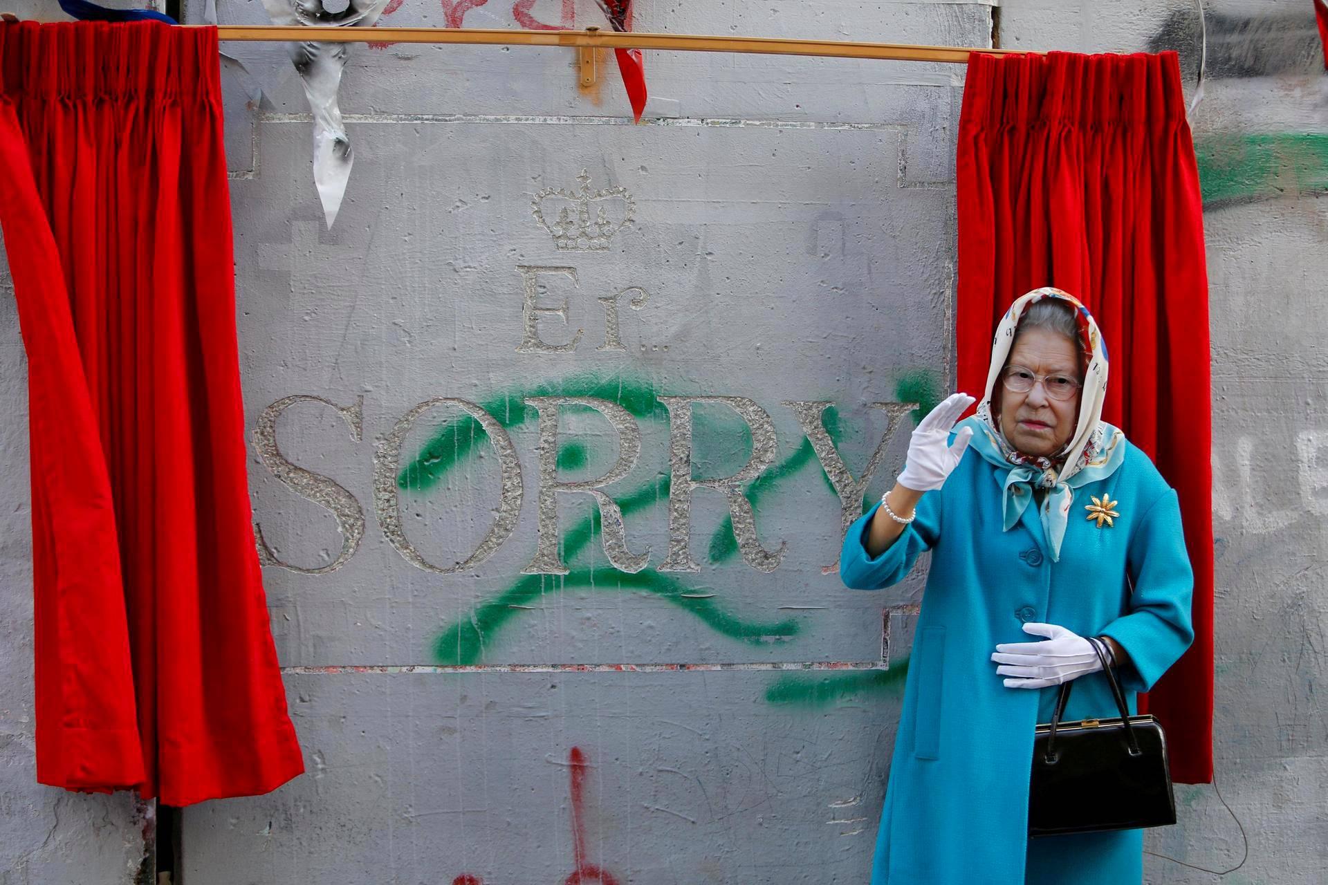 Kuningatar Elisabet II:ksi pukeutunut henkilö vilkutti taiteilija Banksyn teoksen edessä Betlehemissä Länsirannalla Balfourin julistuksen vuosipäivän alla. 100 vuotta sitten annetussa julistuksessa Britannian hallitus ilmoitti tukevansa juutalaisten oman valtion perustamista Palestiinaan.