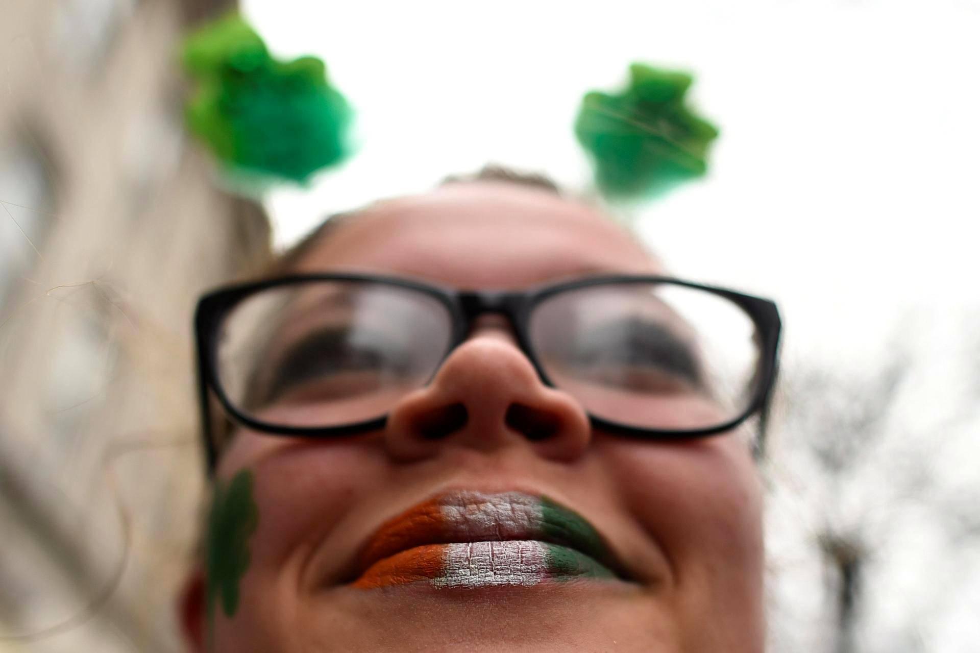 Nainen on maalannut huulensa Irlannin lipun värein perjantaina Dublinissa järjestetyssä Pyhän Patrikin päivän paraatissa.
