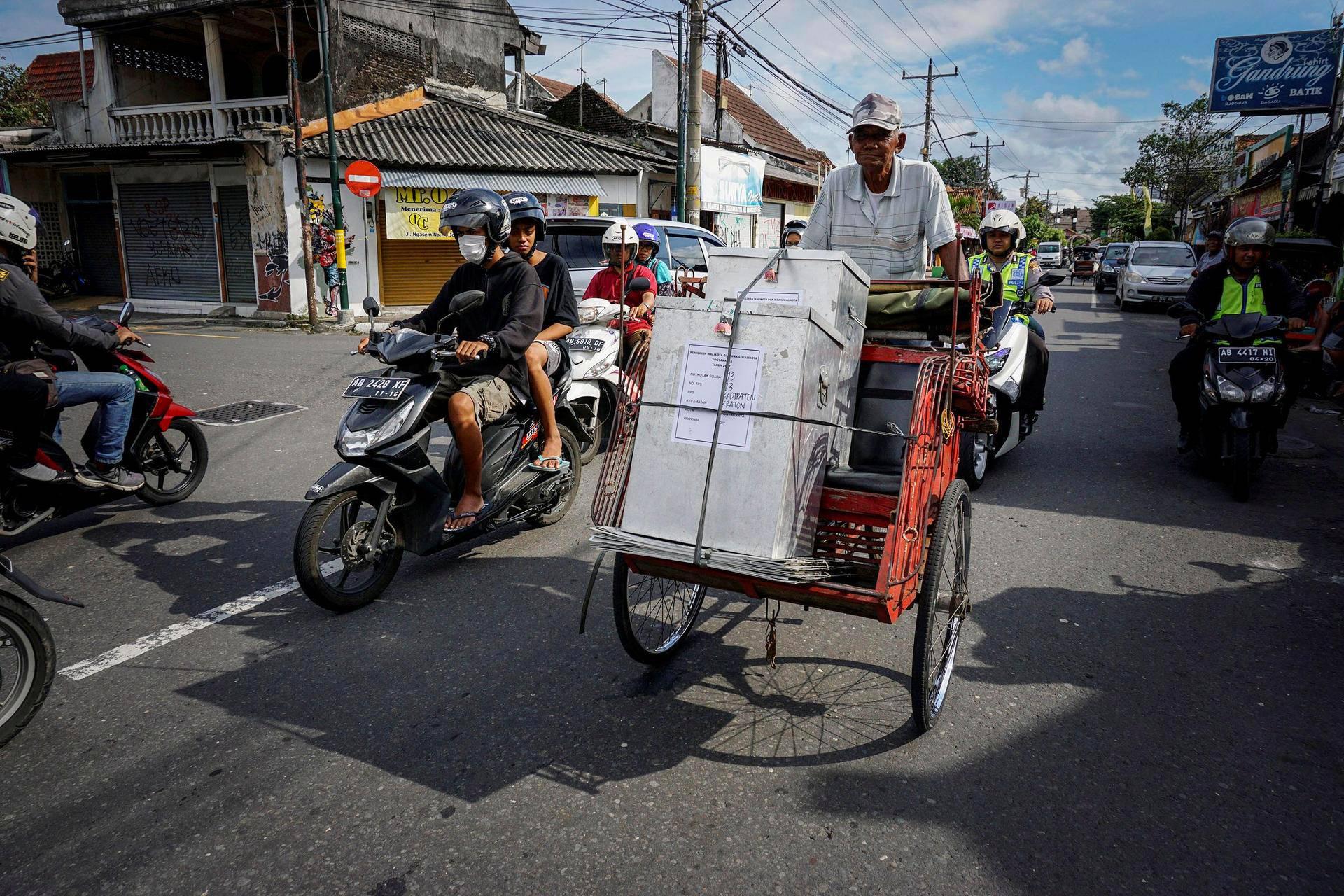 Mies kuljetti äänestyslaatikoita poliisisaattueessa Yogyakartassa Indonesiassa.