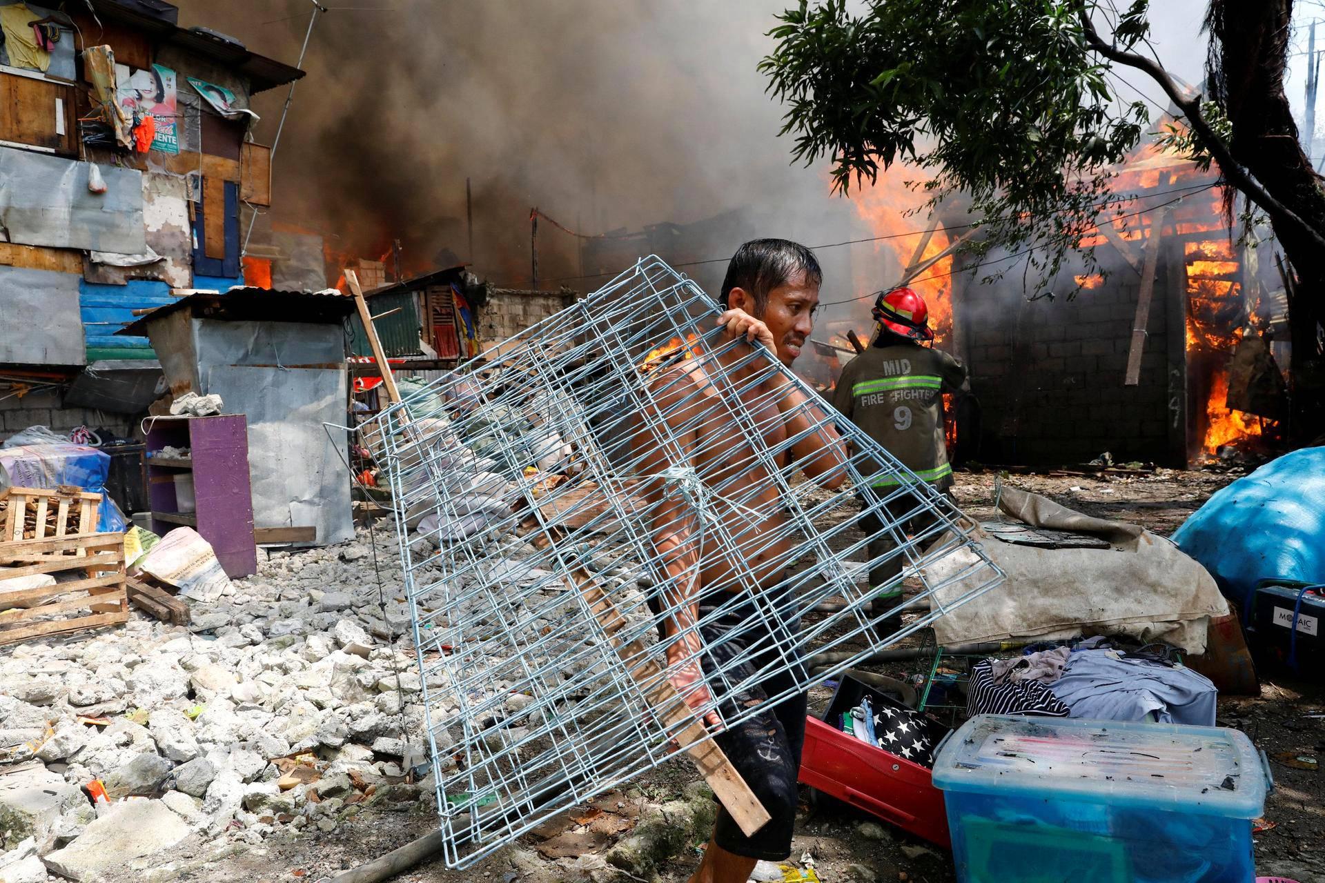 Asukas kantoi tavaroitaan palavien hökkelien ohi Quezon Cityssä Filippiineillä.