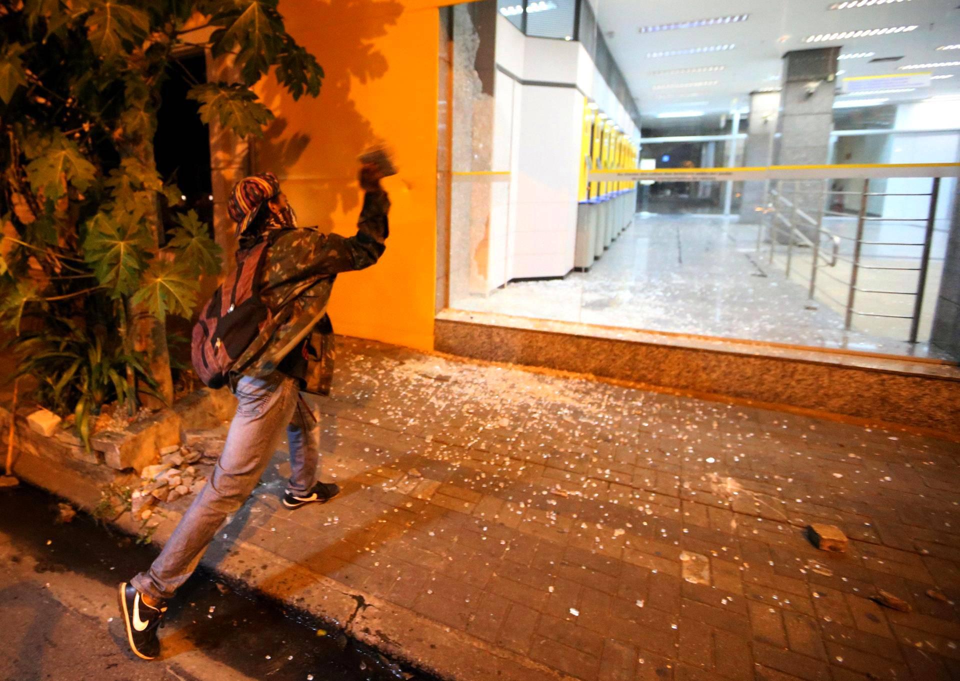 Mielenosoittaja heittää kiven pankin ikkunaan São Paulossa. Bussi- ja metrolippujen hintoihin suunnitellut korotukset ovat aiheuttaneet väkivaltaisia protesteja Brasiliassa.