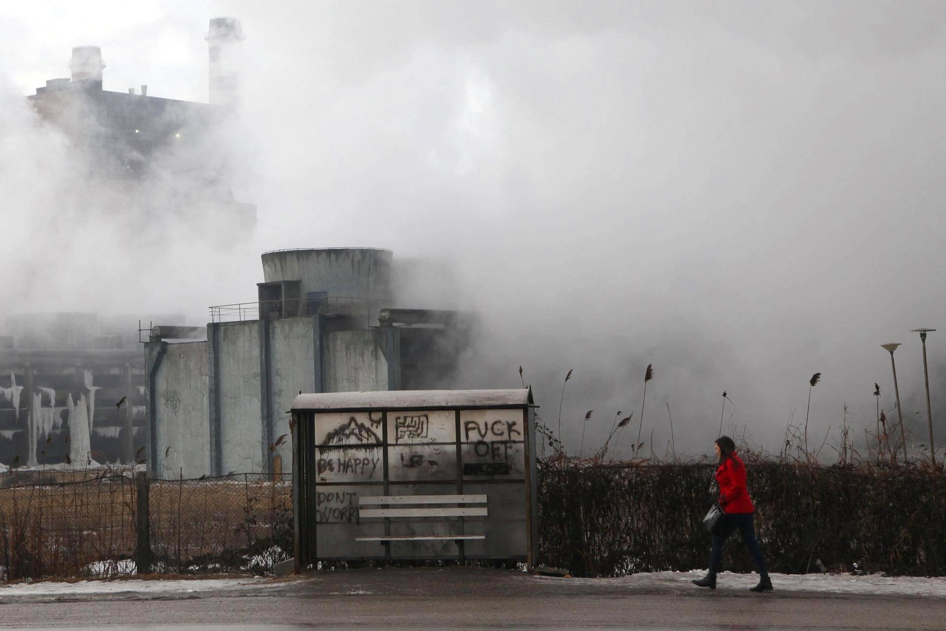 Nainen kulki kohti bussipysäkkiä hiilivoimalan lähellä Pristinassa Kosovossa.