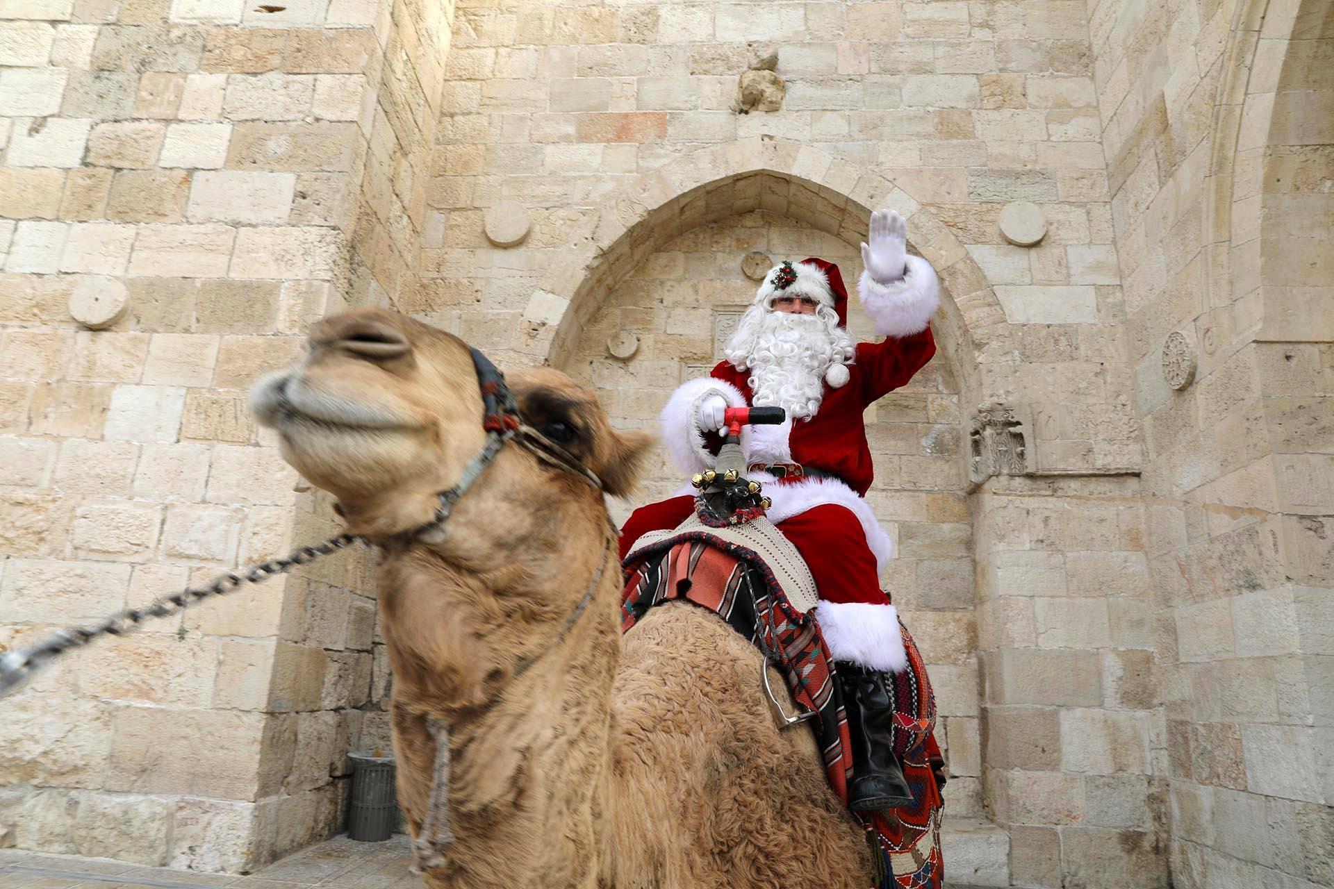 Joulupukki kulki poron sijaan kamelilla Jerusalemin vanhassakaupungissa järjestetyssä joulukuusitapahtumassa.