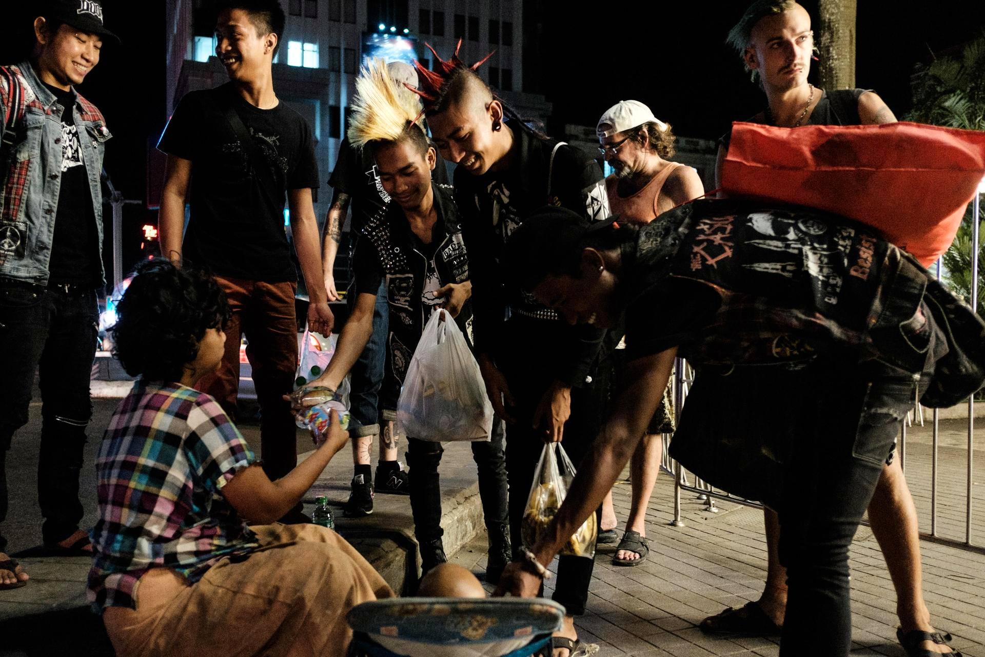 Food Not Bombs -liikkeeseen kuuluvat Ko Hein (vas.), Lin Thaw, Min Zaw Win, Kyaw Kyaw ja Kyaw Awgyi antavat ruokaa Myanmarin suurimman kaupungin Yangonin kadulla asuvalle naiselle.