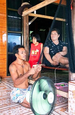 """Jos Kwan Srisook ja Athitaya """"Jom"""" Srisamor eivät pääse Suomeen poimimaan marjoja, myös tyttären Ungkana Srisookin koulunkäynnin rahoittaminen on vaikeaa. Kwan Srisook punoo työpäivän jälkeen kalaverkkoa."""