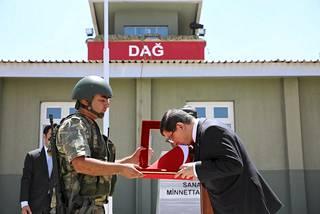 Turkin pääministeri Ahmet Davutoglu suuteli lippua vierilaullaan Dagin sotilastukikohdassa Turkin ja Syyrian välisellä rajalla lauantaina.