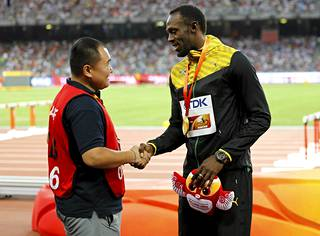 Kameramies Song Tao ja Usain Bolt kättelivät miesten 200 metrin palkintojenjaon yhteydessä.