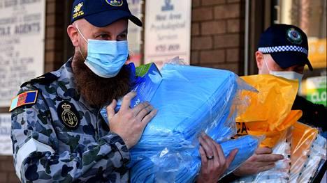 Australian armeija auttaa maan suurinta kaupunkia pitkittyneen koronasulun toteuttamisessa. Puolustusvoimien työntekijä (vas.) ja poliisi veivät suojavarusteita jaettavaksi Fairfieldin esikaupunkialueelle Sydneyssä 3. elokuuta.