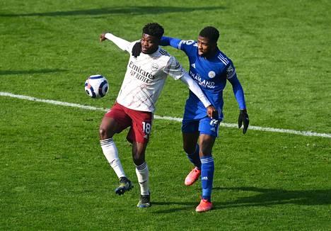 Leicesterin Kelechi Iheanacho (oik.) on ottanut tukevan otteen Arsenalin Thomas Parteysta, joka yrittää suojata palloa.