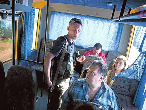 Sergeiksi esittäytynyt asemies tarkasti matkustajia Mariupolista Donetskiin saapuvassa bussissa Venäjän-mielisten separatistien tiesululla Donetskin ulkopuolella.