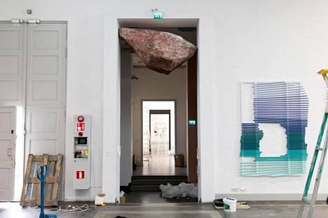 Raimo Saarisen teos Graniittilohkare (2019) roikkuu oviaukossa. Se koostuu vesiväristä, paperista ja kasviliimasta.