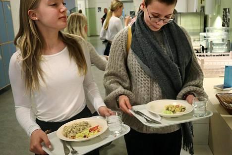 Kruununhaan yläasteen koulussa oli viime maanantaina ruoaksi liha-makaronilaatikkoa ja kasvispastavuokaa. Emma Lahti (vas.), Ella Leino ja Leoni Riste (takana) haluaisivat selvästi näkyviin luvut hukkaan menevästä kouluruoasta.