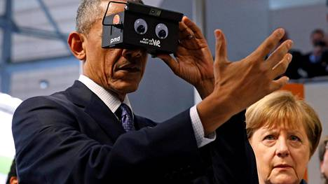 Barack Obama kokeili virtuaalitodellisuuslaseja Hannoverin messuilla sunnuntaina. Liitokansleri Angela Merkel seurasi vierestä.
