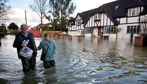 Paikalliset asukkaat kahlasivat tulvavedessä Wraysburyn kylässä Englannin Berkshiressä maanantaina.