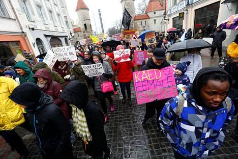 """Viron konservatiivisen kansanpuolueen Ekren hallituspaikkaa vastustavat ihmiset marssivat Tallinnassa maaliskuun lopulla. Kylteissä käskettiin populisteja pitämään """"näpit irti feministeistä"""" sekä rakastamaan totuutta ja tiedettä. Lisäksi niissä todettiin, että Ekren ottaminen hallitukseen on """"niin häpeällistä""""."""