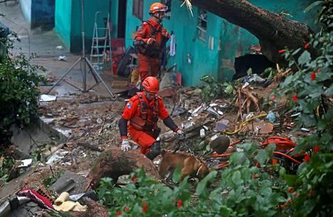 Pelastustyöntekijät etsivät uhreja koiran kanssa Rio de Janeirossa tiistaina.