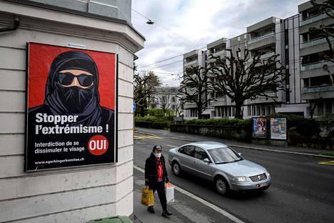 """Kasvomaskiin sonnustautunut mies käveli """"burkakieltoa"""" vaativan julisteen ohi Sveitsin Lausannessa torstaina."""