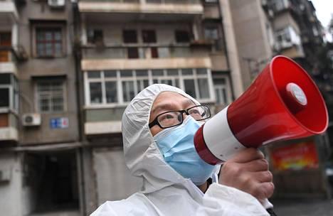 Työntekijä tiedottaa terveystarkastuksista asuinalueella Wuhanissa.