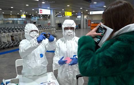 Työntekijät tarkistavat epidemia-alueelta saapunutta matkustajaa lentokentällä Moskovassa 10. maaliskuuta.