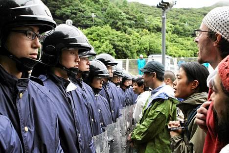 Mielenosoittajat seisoivat poliisirivistön edessä lähellä Oin ydinvoimalaa.